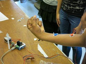 A student experiments with sensor placement and arm movement to determine the effects of different variables on the speed of the motor.