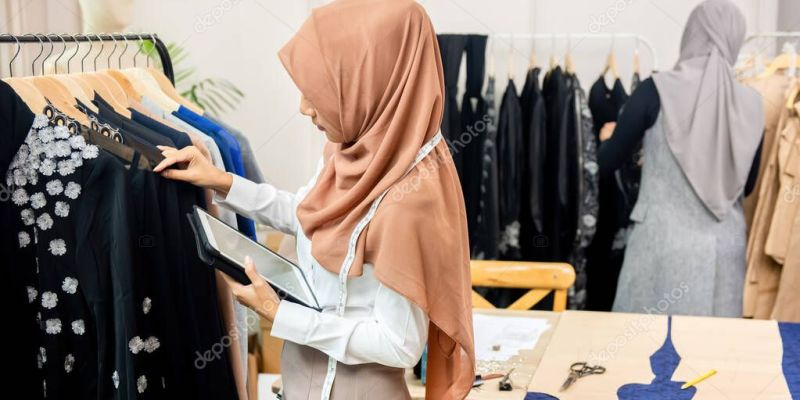 Woman muslim designer holding a tablet while checking hanged clothes in a garment boutique shop