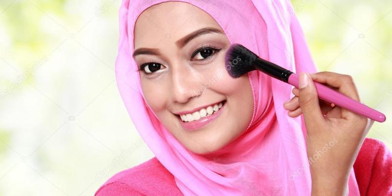young muslim woman applying blush on
