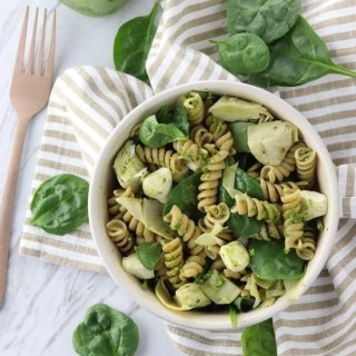 Spinach and artichoke whole wheat pesto pasta salad on a napkin from above