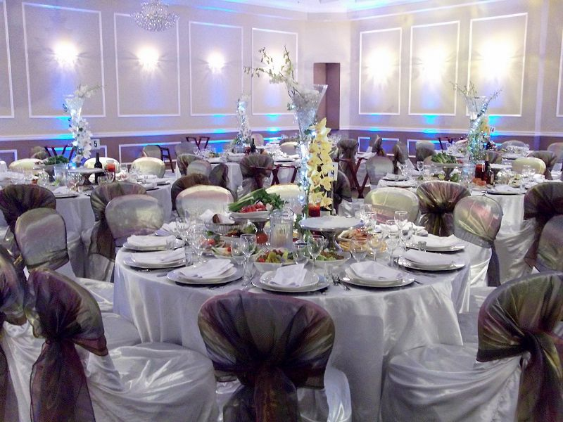This indoor wedding setup emphasizes satiny white with silvery overtones