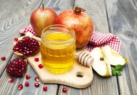 honey apple and pomegranate on wooden table