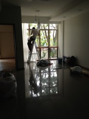 Curtain installer putting on the layer of sheer at our living hall