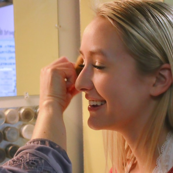 applying custom eyshadow loose mineral eyeshadow on happy girl in mirror