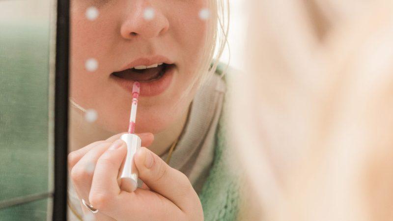 putting on custom lip gloss in the mirror
