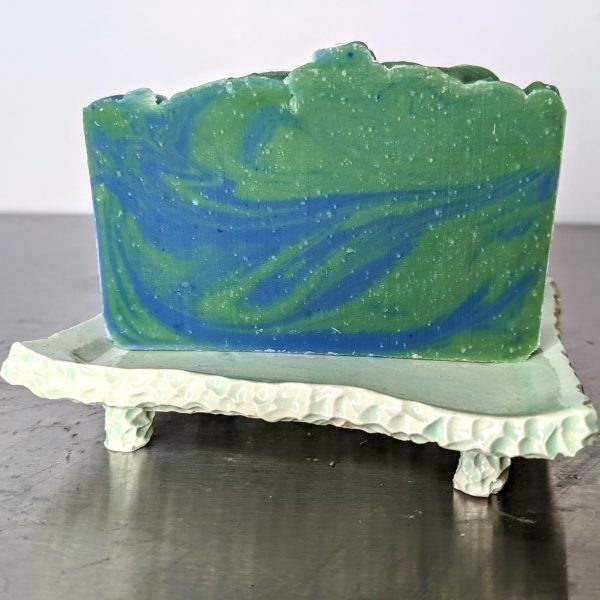 green and blue earth and water soap made with organic ingredients using an in the pot swirl method on a ceramic soap dish scented with kaffir lime and patchouli essential oils
