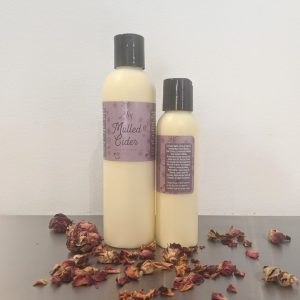 organic moisturizing mulled cider body lotion with plum label, rose petals and scented with essential oils