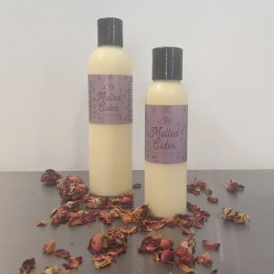 two bottles of organic mulled cider lotion with rose petals and scented with essential oils