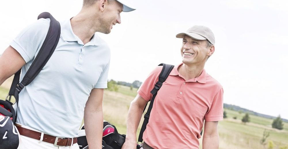 Happy male golfers conversing against clear sky