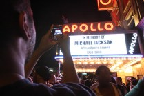 FILE - In this June 25, 2009 file photo, Tshaka Lafayette, of New York, left, takes a picture of the marquee at the Apollo theater as people gather to remember Michael Jackson in the Harlem neighborhood of New York, after Jackson, 50, died in Los Angeles. (AP Photo/Tina Fineberg, File)