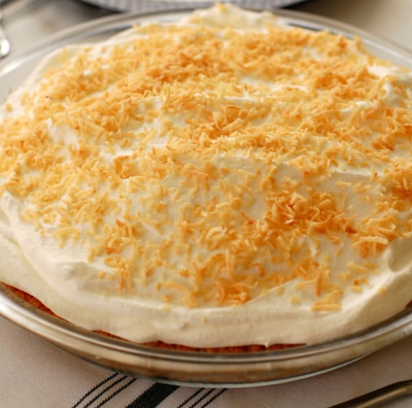 With a thick layer of sweetened whipped cream flavored with coconut rum and a sprinkling of toasted coconut, piña colada pie is ready to be sliced and served. | mjbakesalot.com