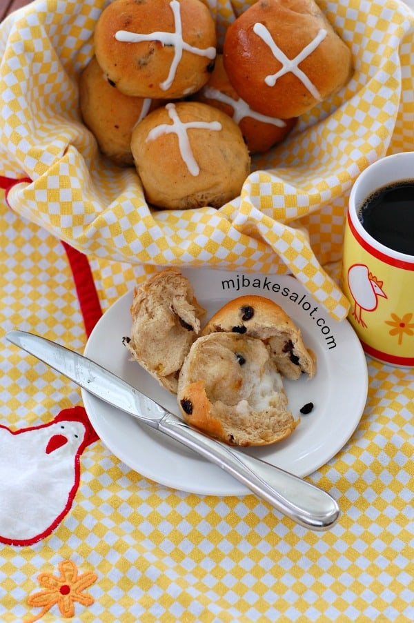 A basket of fragrant hot cross buns that are still warm from the oven, accompanied by good butter, and a mug of coffee. | mjbakesalot.com