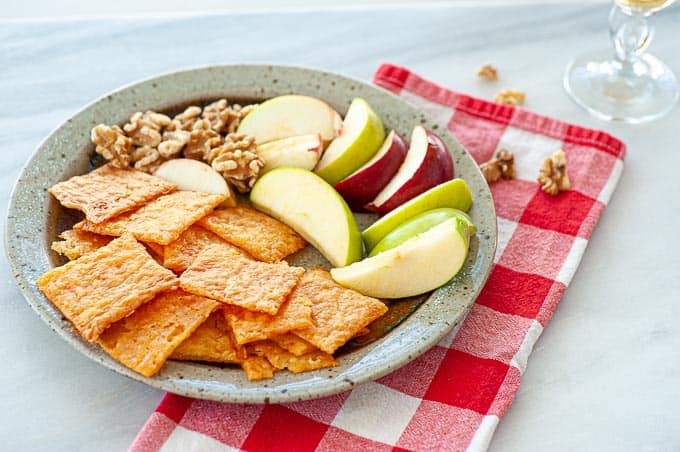 Easy cheesy sourdough crackers shown with toasted walnuts and slices of juicy apple.