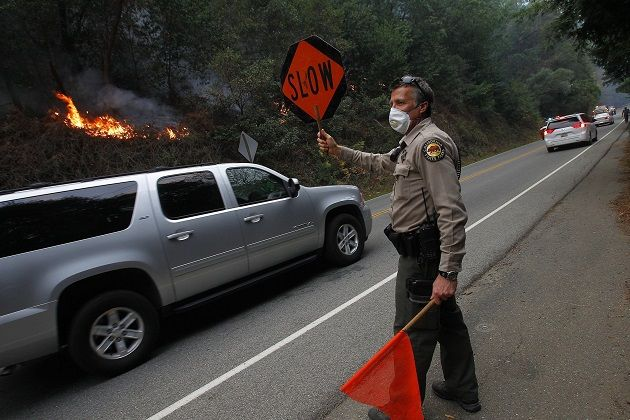 A park ranger directs traffic along Highway 1 as the Big Sur fire burns nearby.