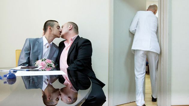 A male couple kisses seated at a table