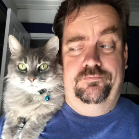 An image of the author with a cat sitting on his shoulder. he's raising an eyebrow and giving the cat side-eye.