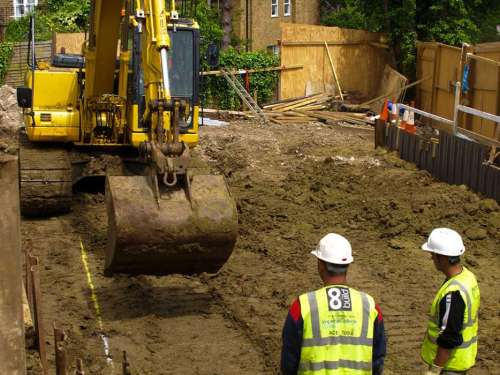 excavator and groundworkers beginning a trench for foundations