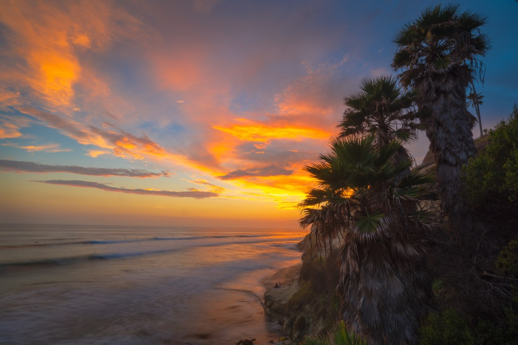 Coastal California Photography warm colored sunset at the beach with couple off in distance watching