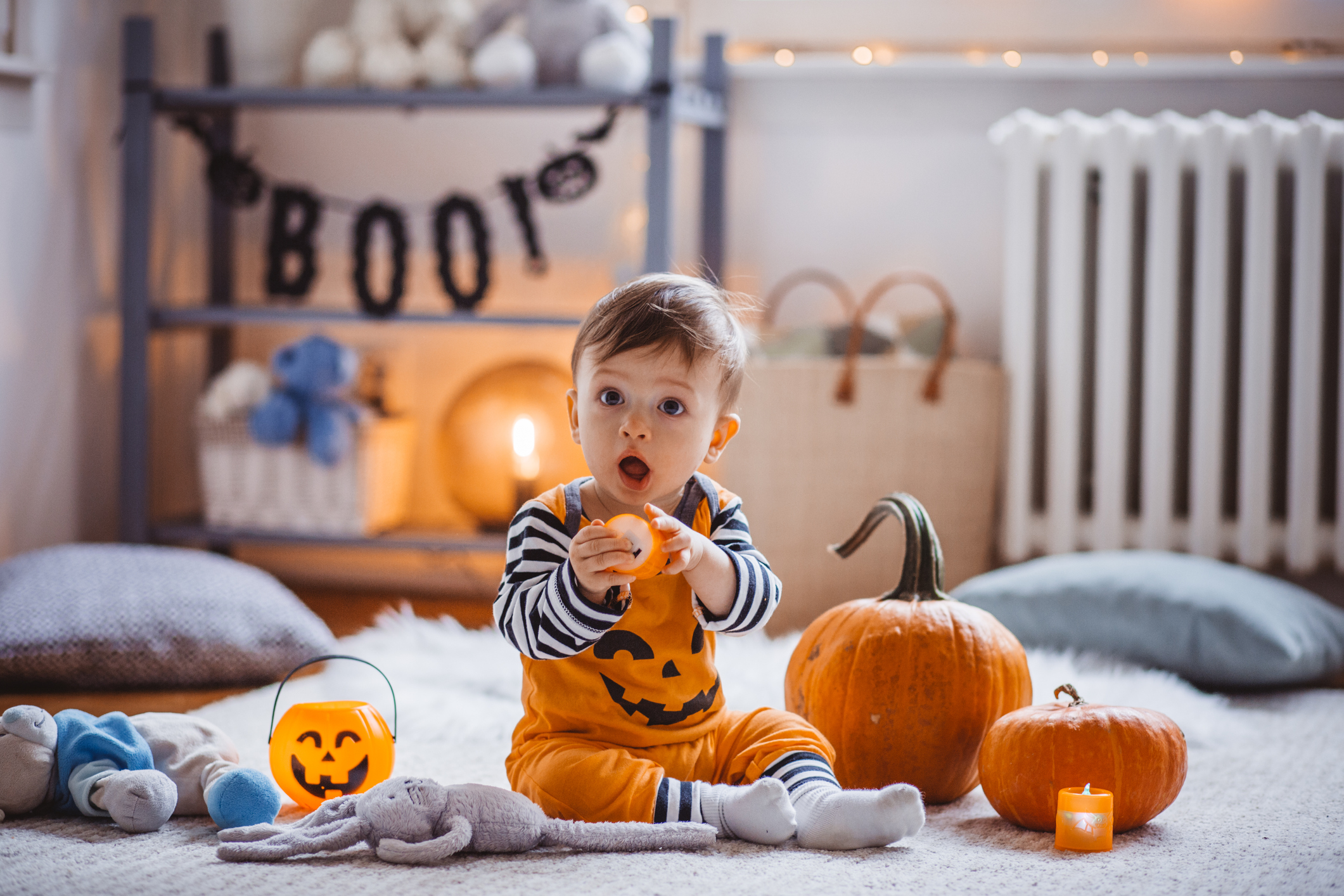 Baby boy wear costume and playing on floor on Halloween