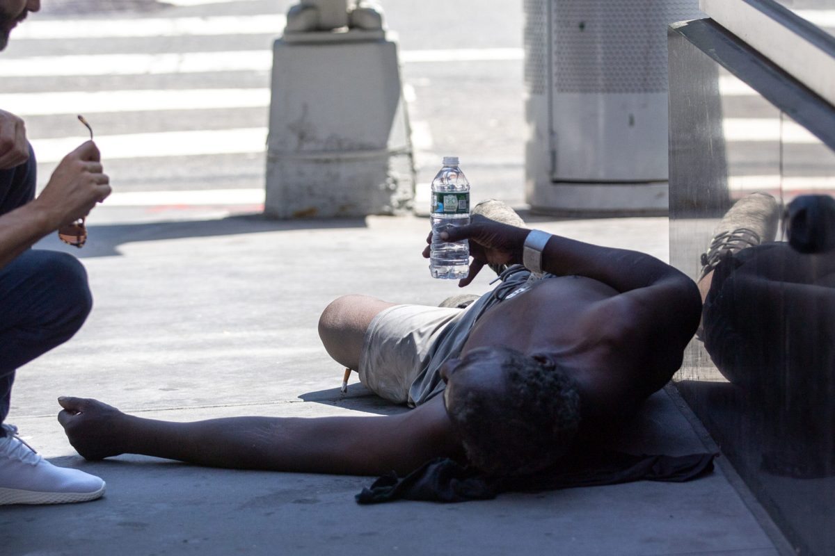 A person lays on the street near Times Square during a heatwave in New York, on Wednesday, June 30, 2021. Credit: Jeenah Moon/Bloomberg via Getty Images