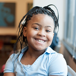 Cute young girl in blue shirt smiling at camera