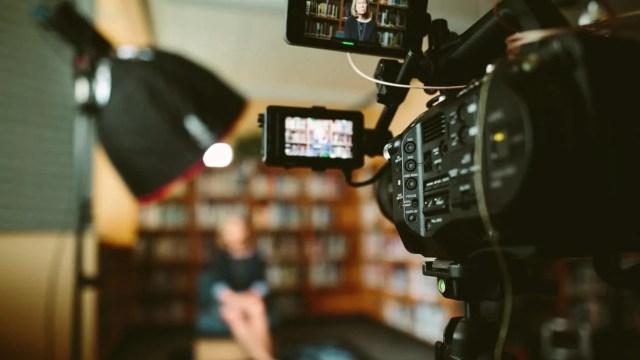 No visor de uma câmera de filmagem está a imagem de uma mulher branca, de cabelos loiros lisos na altura do ombro e roupas pretas em frente a uma estante de livros. Ao fundo da câmera, a mesma cena está desfocada, com uma grande softbox preta de iluminação sobre um tripé.