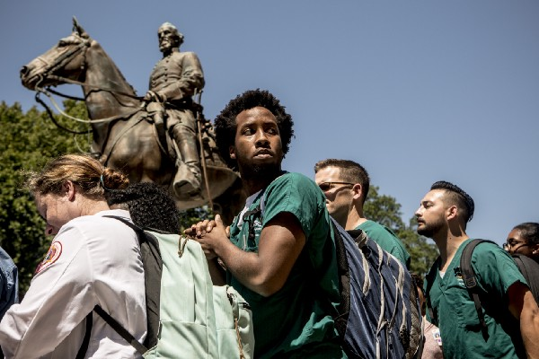 Students from University of Tennessee Health Science Center protest next to a statue of Nathan Bedford Forrest.