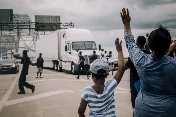 Protesters, with hands reaching up, block a tractor trailer from driving on Hernando DeSoto Bridge