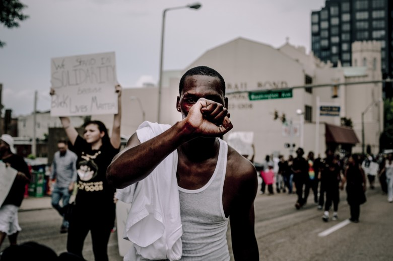 Black protester holding up fist while walking down street