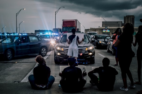 Protesters sit in road blocking cars
