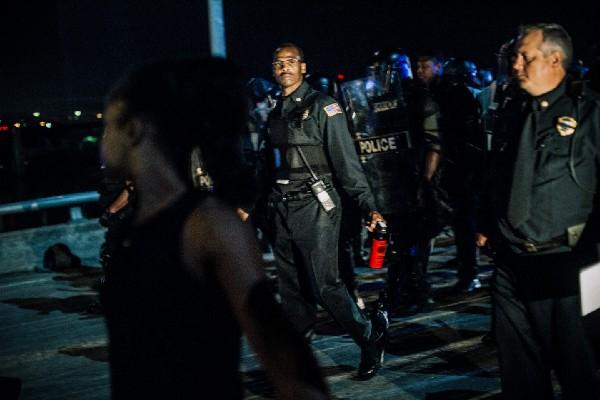 Memphis police officers walk across Hernando DeSoto Bridge at night