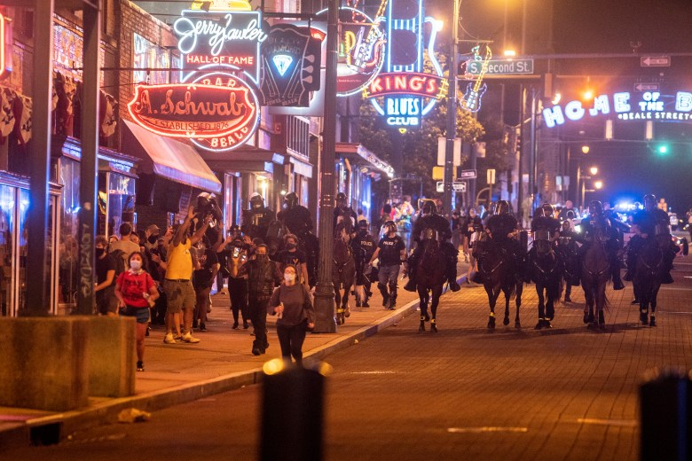 Memphis police on horseback clear Beale Street during a protest.