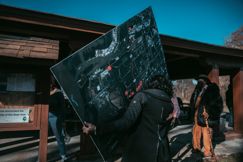 A woman carries a large poster board of a map.