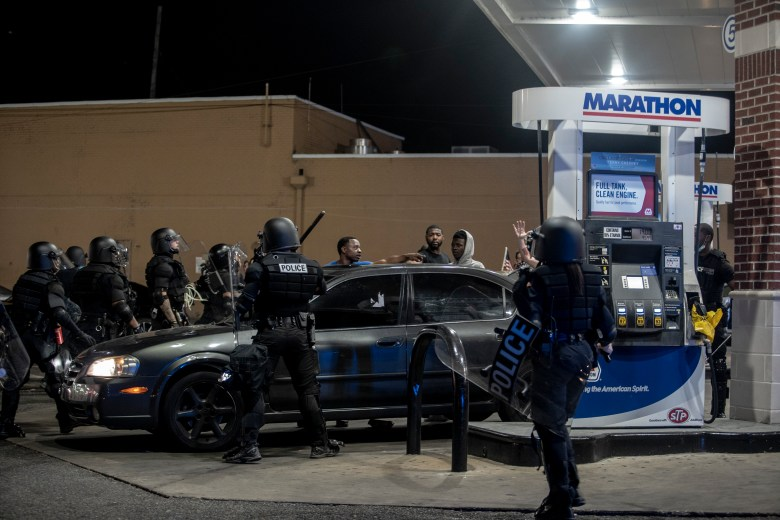 Memphis police in riot gear surround a car at a gas station.