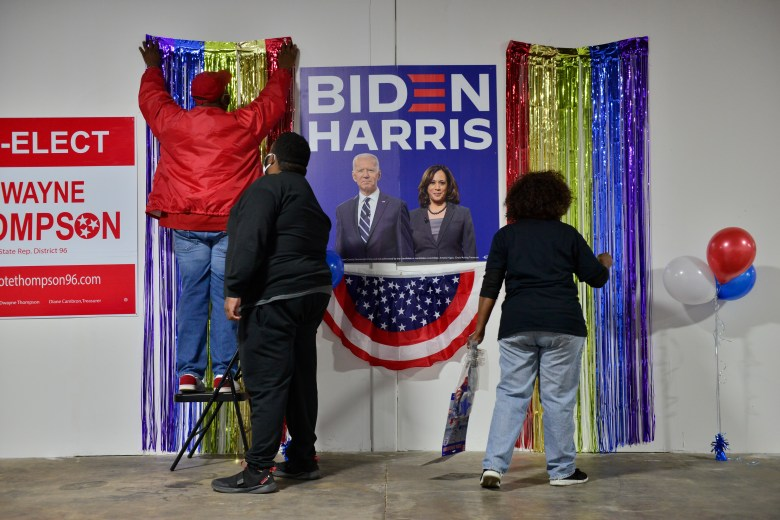 Three people hang streamers and balloons inside a building. Between them is an election poster featuring Joe Biden and Kamala Harris.