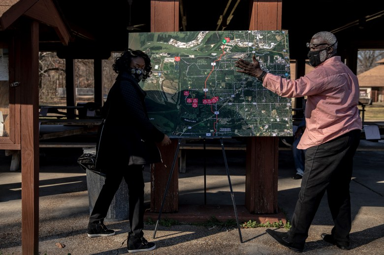 A man and woman place a map on an easel during a community meeting about the Byhalia pipeline.