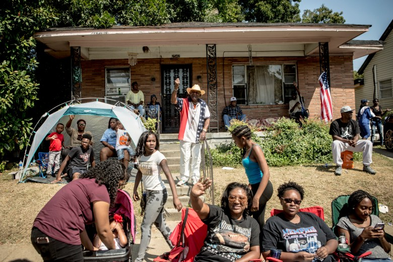A group of Black men, women and children gather on the front lawn of a home to watch the Southern Heritage Classic parade.