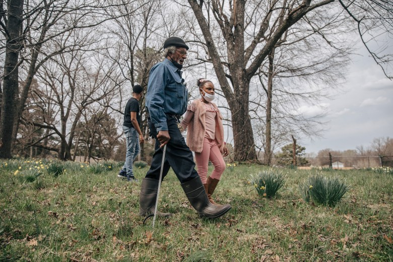 Clyde Robinson walks his property in Southwest Memphis with his granddaughter Aareona Ginns.