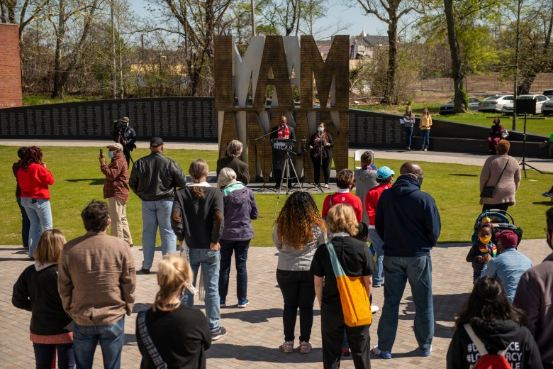 A socially distance crowd listens to speakers in front of the I AM A MAN sculpture in Memphis.