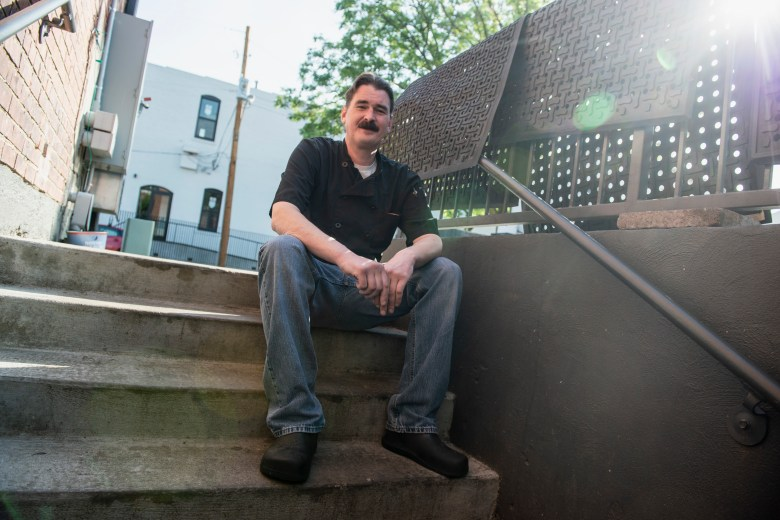 Pete DeQuattro, a restaurant worker in Memphis, sits on a flight of concrete stairs.