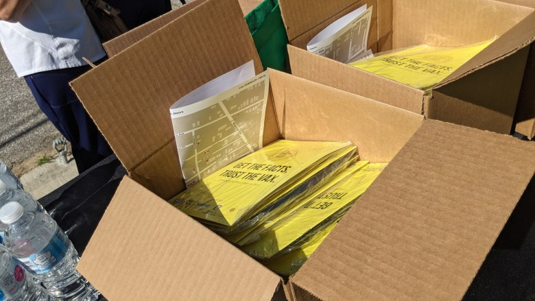 Pamphlets about vaccination are stacked inside a cardboard box.