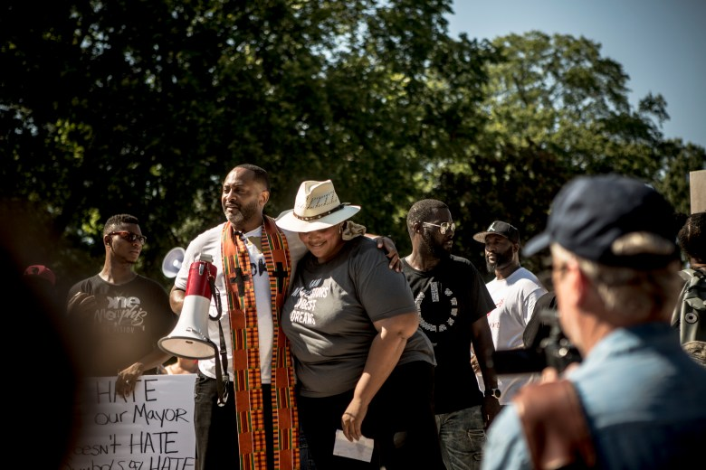 Rev. Earle Fisher and Tami Sawyer embrace during a demonstration.