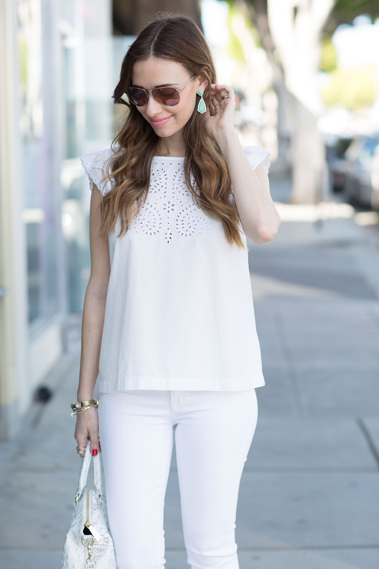 white embroidered top with white jeans and aqua earrings