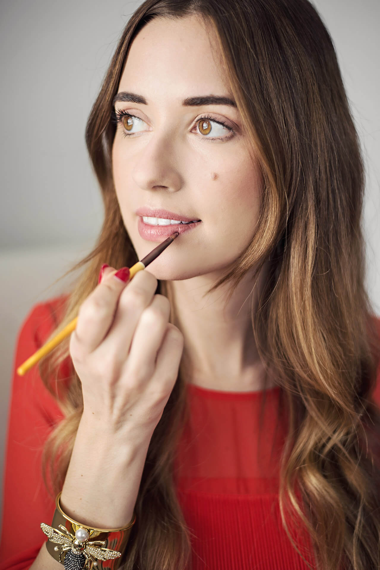 applying lipstick with a lip liner brush allows for a more polished pout
