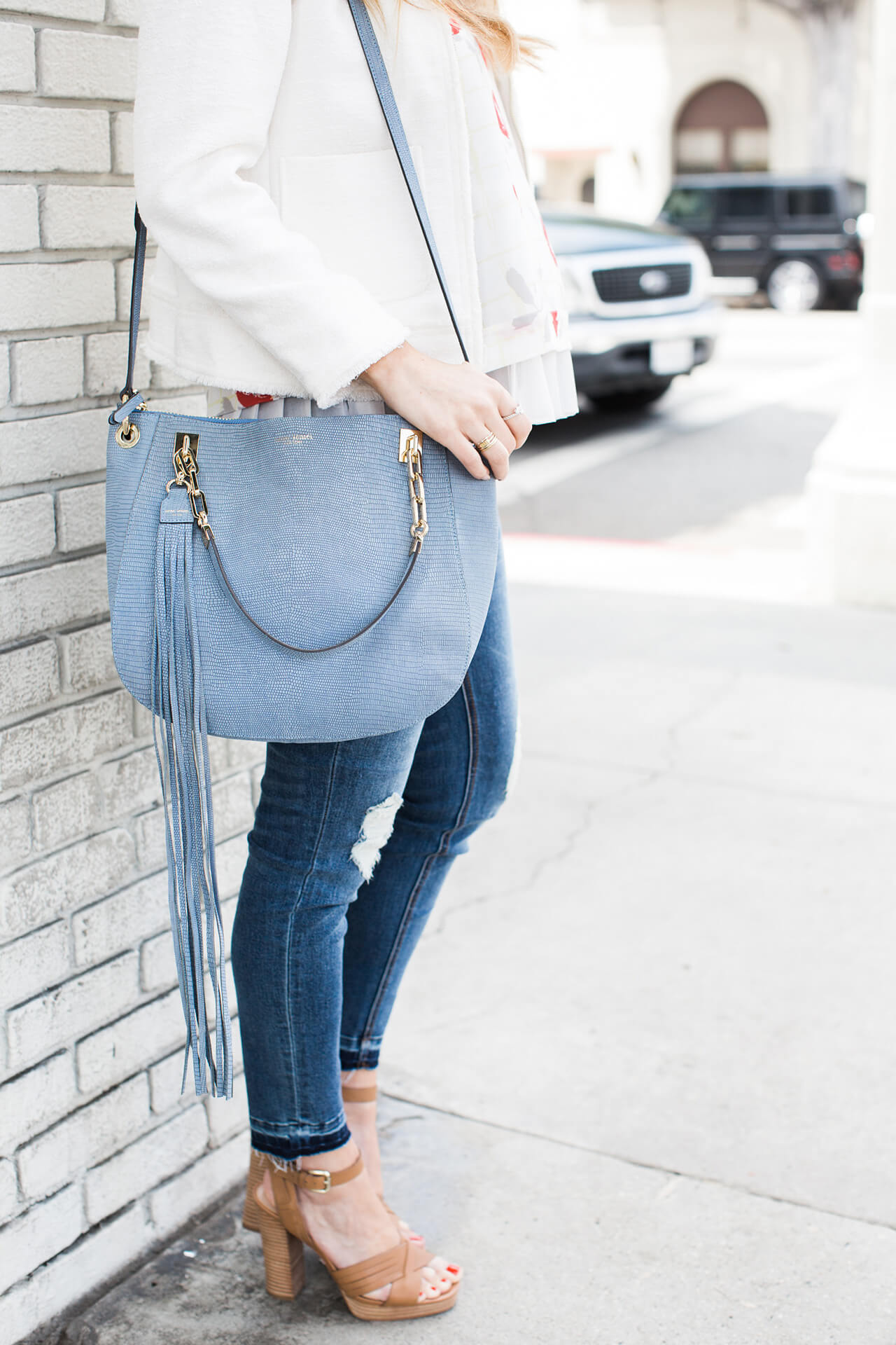 blue satchel bag with fringe and skinny jeans with sandal heels