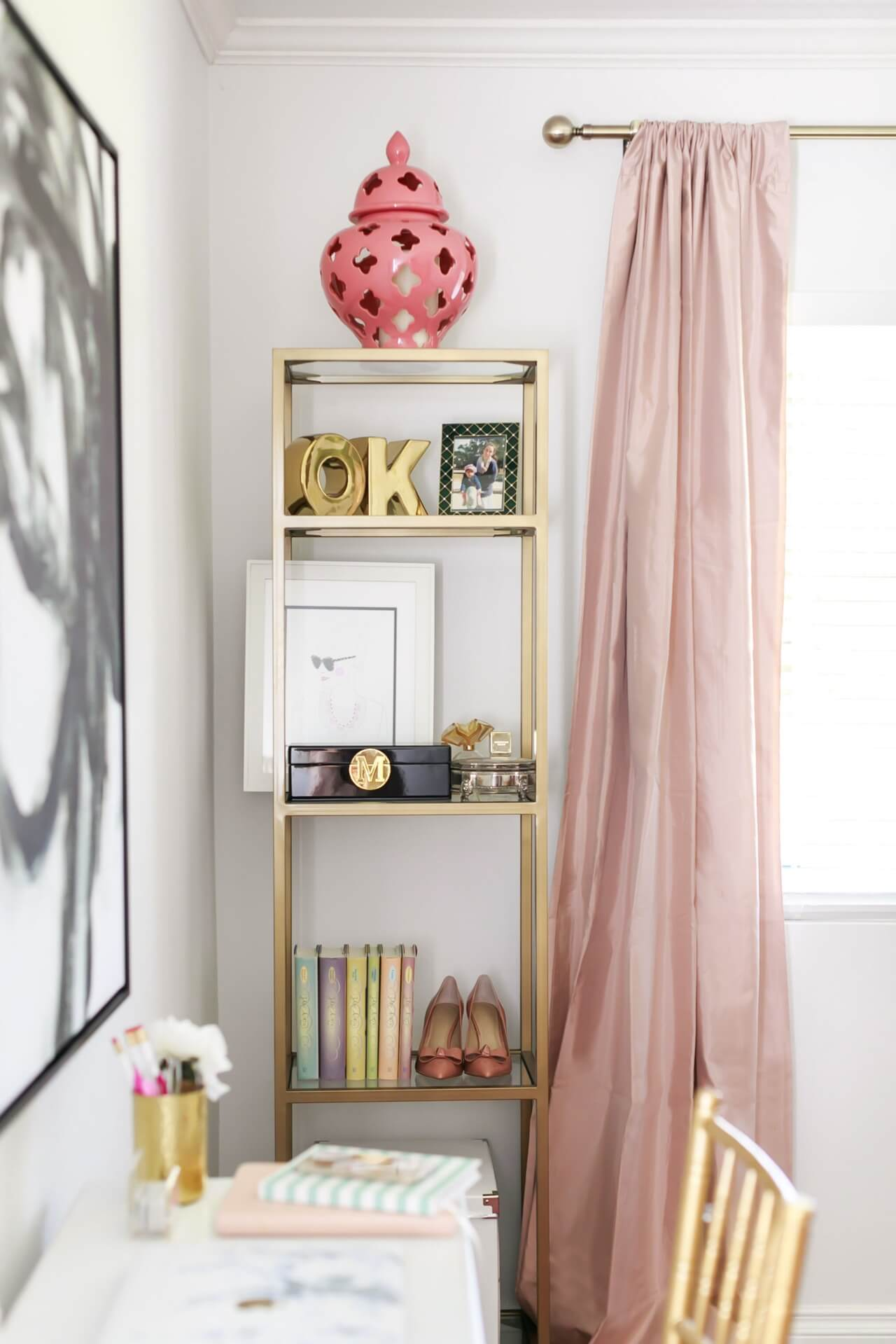 gold and glass bookshelves with pink satin curtains