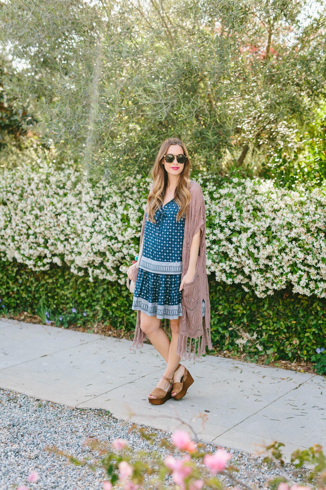 a blue drop waist dress with crochet maxi cardigan