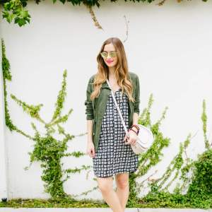 casual summer outfit with bold black and white print and green field jacket