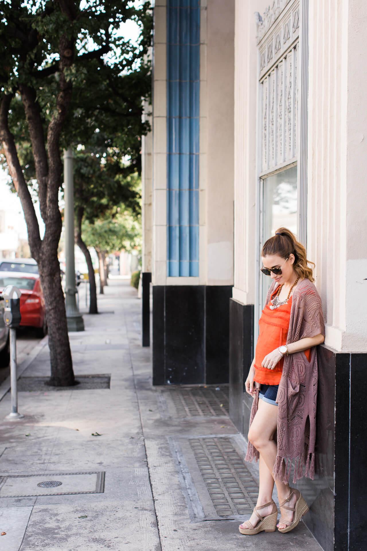 summer maternity outfit inspiration with orange fringe tank, denim shorts, and maxi cardigan