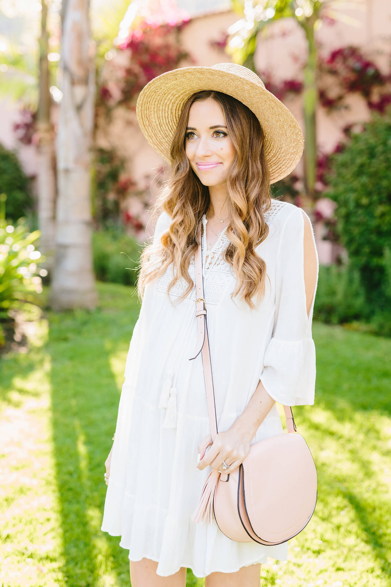 white bohemian dress with sun hat and pink bag